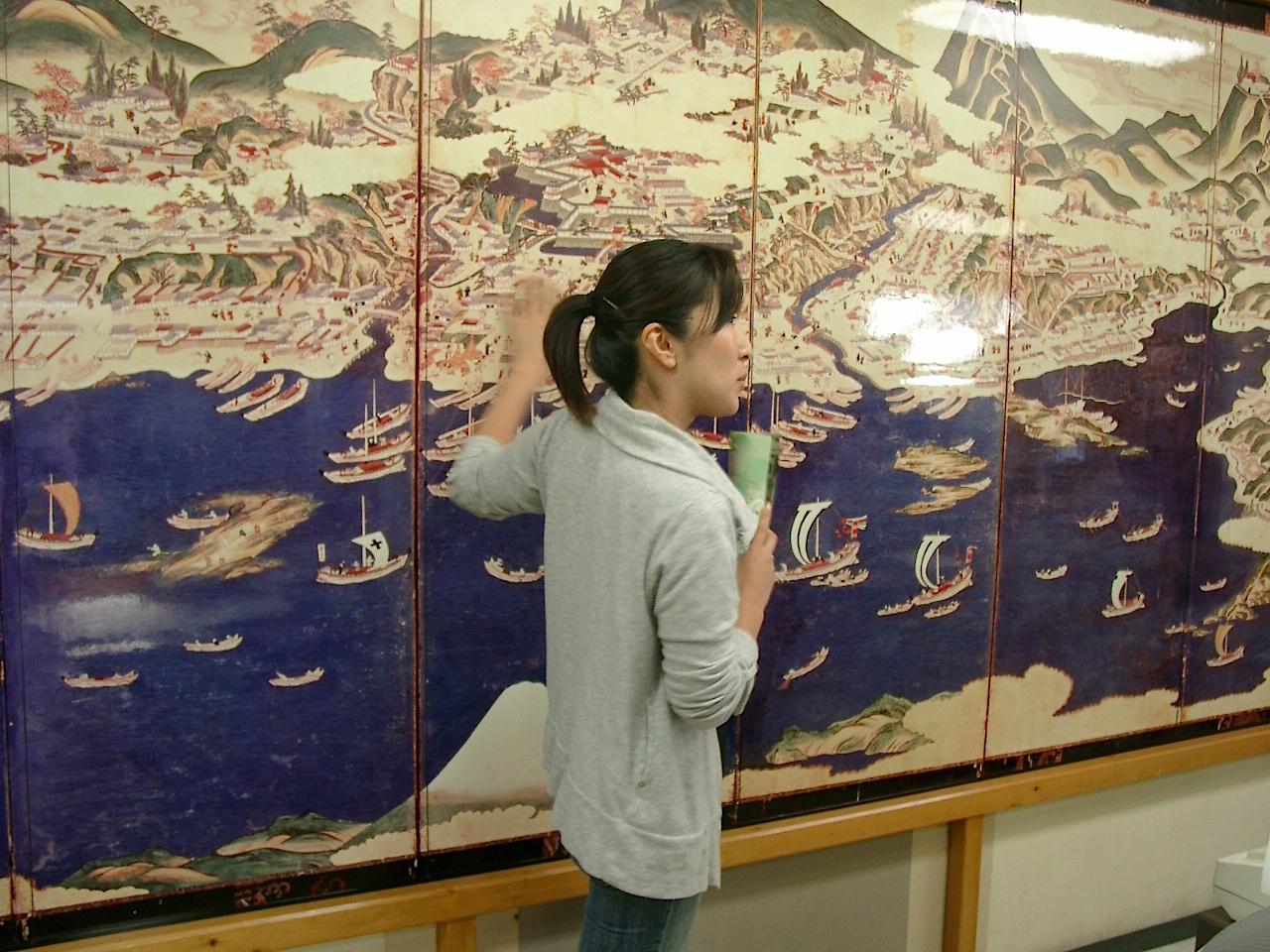 温泉旅館矢野に展示される松前屏風図(レプリカ)を解説する若女将の杉本夏子さん